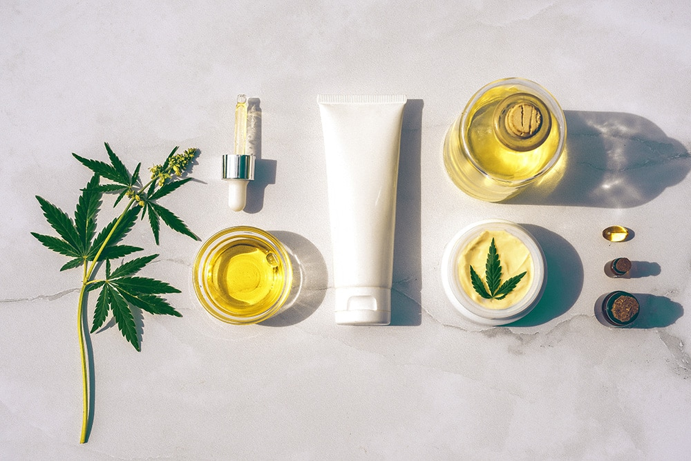 CBD Oil, CBD Capsules and CBD Cream on white marble.