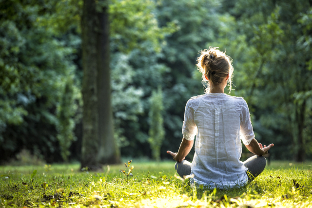 Woman experiencing high-strength CBD oil whilst meditating in a park