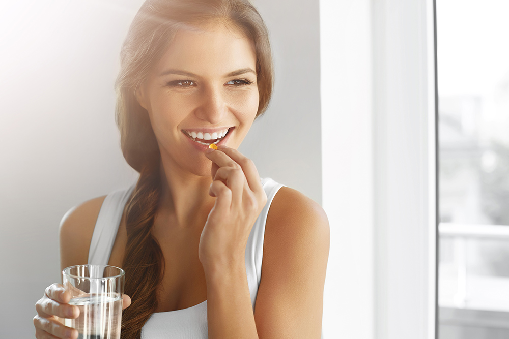 Woman taking a CBD Softgel and smiling